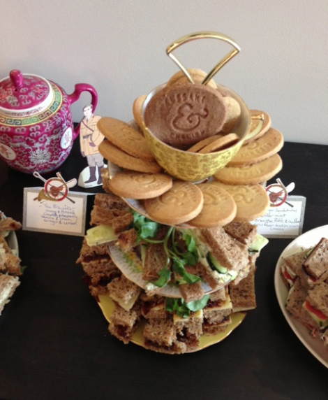 A photo of a cake stand with biscuits and finger sandwiches