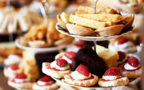 A photo of Vintage style cake stands piled with cakes and sandwiches