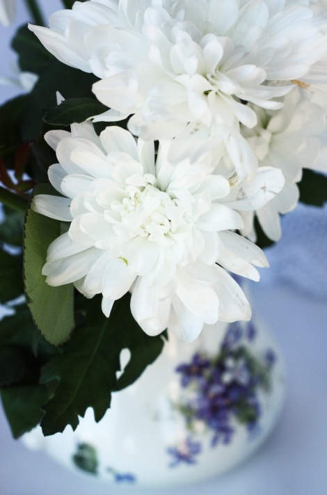 a photo of White flowers in vintage china jug