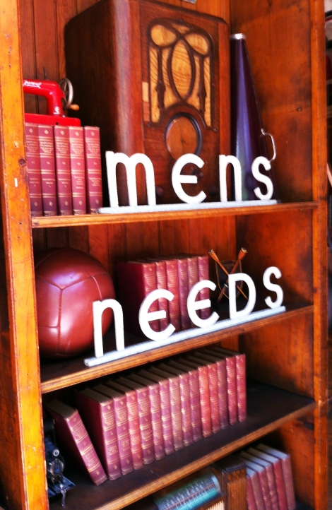 A photo of a retro sign in a men's clothes shop spelling 'Men's Needs'
