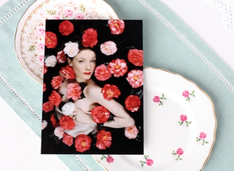 Blumenfeld postcard of from Picture Post photo shoot on top of some vintage rosebud china