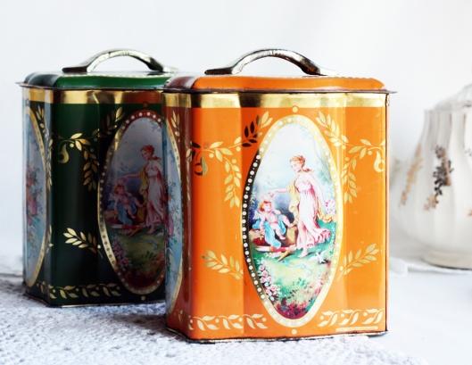 A photo of orange and green vintage tin tea caddies