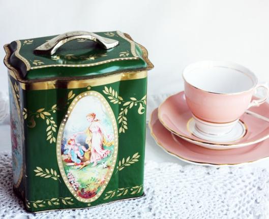 A photo of a green vintage tin tea caddy